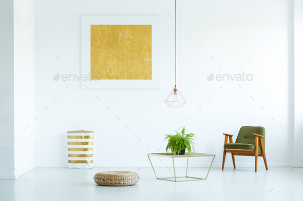 Table with plant between pouf and green armchair in white flat i - Stock Photo - Images