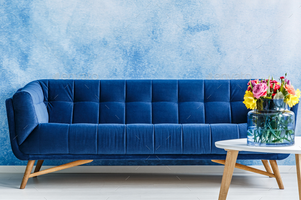 Comfortable navy blue plush sofa and colorful flowers in a vase - Stock Photo - Images