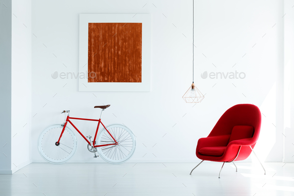 Bike and red armchair set on a white wall with a simple painting - Stock Photo - Images
