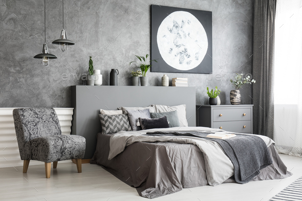 Armchair next to bed in grey bedroom interior with moon poster o - Stock Photo - Images