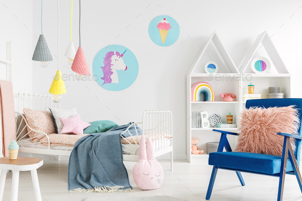Furry pink pillow on a vibrant blue armchair in a sweet kid bedr - Stock Photo - Images