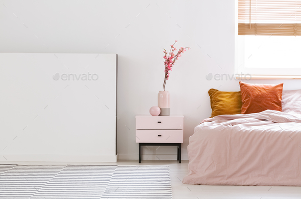 Real photo of a pink, feminine bedroom interior with orange cush - Stock Photo - Images