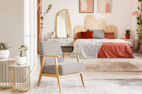 Patterned wooden armchair next to gold table in orange bedroom i - Stock Photo - Images