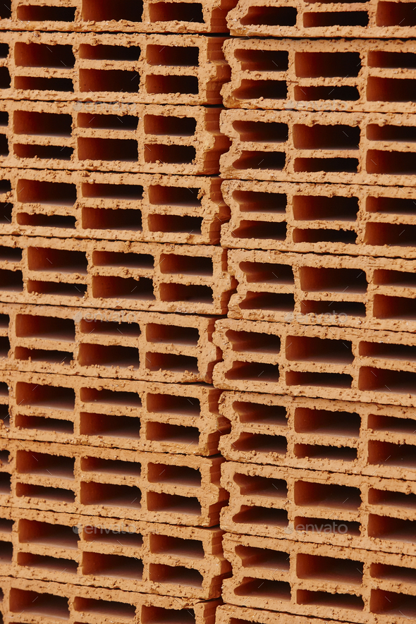 Stacked orange bricks. Construction industry. Building pieces. Vertical - Stock Photo - Images