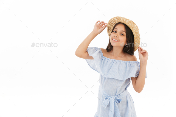 Smiling young brunette girl in dress and straw hat posing - Stock Photo - Images