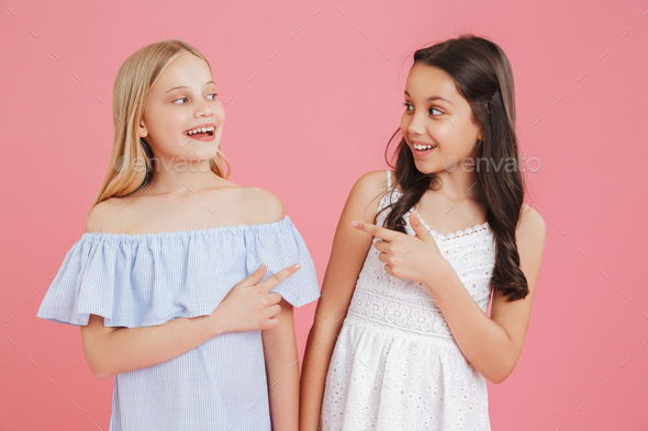 Photo of cheerful little girls 8-10 years old wearing dresses sm - Stock Photo - Images