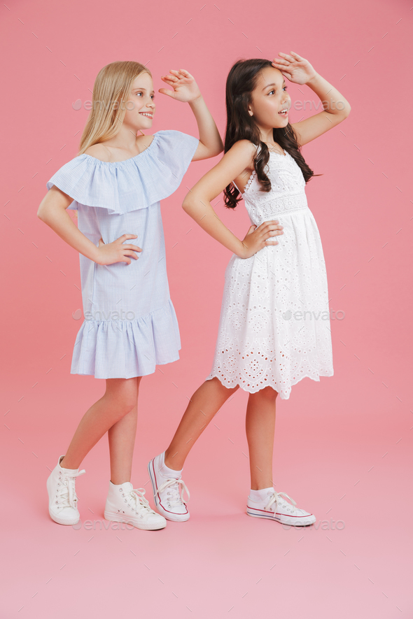 Full length photo of joyful girls wearing dresses smiling and lo - Stock Photo - Images