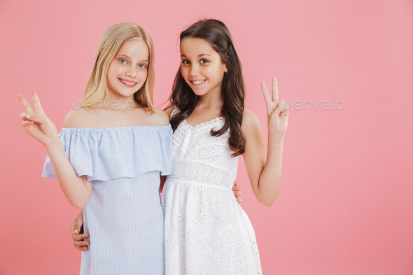 Image of two beautiful girls 8-10 years old wearing dresses smil - Stock Photo - Images