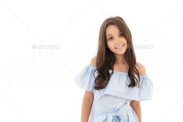 Smiling young brunette girl in dress looking at camera - Stock Photo - Images