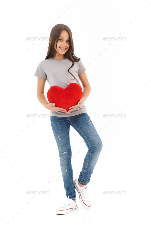 Cute girl standing isolated holding heart in hands. - Stock Photo - Images