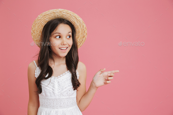 Excited european girl 8-10 wearing white dress and straw hat loo - Stock Photo - Images