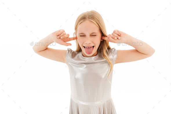 Angry young blonde girl in dress screaming and covering ears - Stock Photo - Images