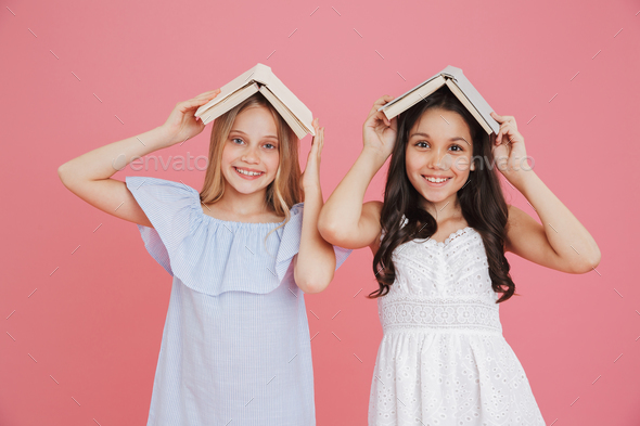 Picture of happy european girls wearing dresses holding books at - Stock Photo - Images