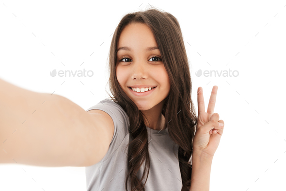 Pretty cute girl make selfie looking camera showing peace gesture. - Stock Photo - Images