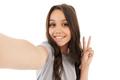 Pretty cute girl make selfie looking camera showing peace gesture. - PhotoDune Item for Sale