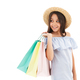Smiling brunette girl in dress and straw hat holding packages - PhotoDune Item for Sale