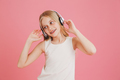 Adorable blonde girl 8-10 in casual clothing listening to music - PhotoDune Item for Sale