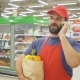 Handsome Delivery Man with Grocery Paper Bag Taking an Order Using a Smartphone in Supermarket - VideoHive Item for Sale