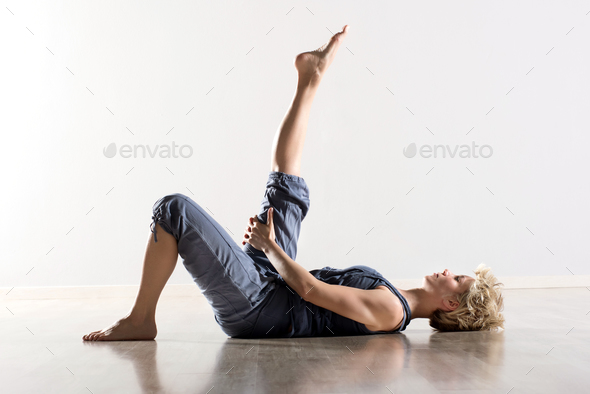 Woman on back stretching hamstring muscles - Stock Photo - Images