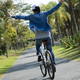 Riding bike with arms outstretched  in park - PhotoDune Item for Sale