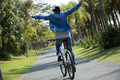 Riding bike with arms outstretched  in park