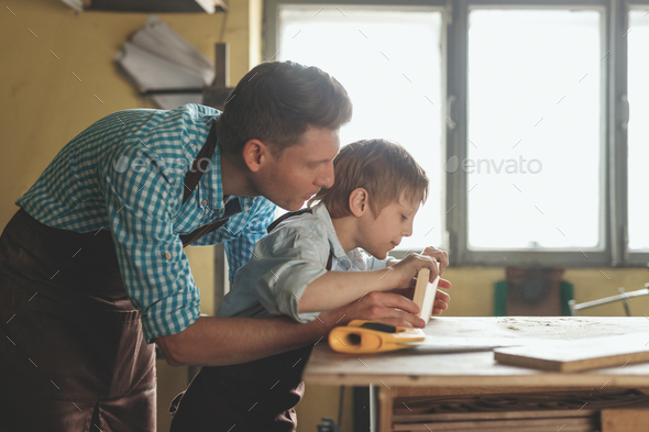 Father and son with a wooden plank - Stock Photo - Images