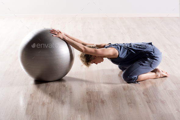 Woman stretching shoulders with fitness ball - Stock Photo - Images
