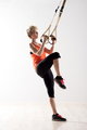 Woman lifting leg and pulling on exercise rings - PhotoDune Item for Sale