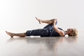 Woman holding knee while stretching hamstring - PhotoDune Item for Sale