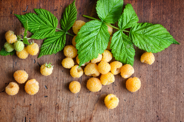 Ripe yellow raspberries with leaves on the old wooden background - Stock Photo - Images