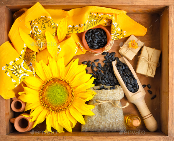 Beautiful composition with sunflower, oil and seeds in bag on wo - Stock Photo - Images