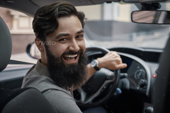 Happy charismatic man driving a car - Stock Photo - Images