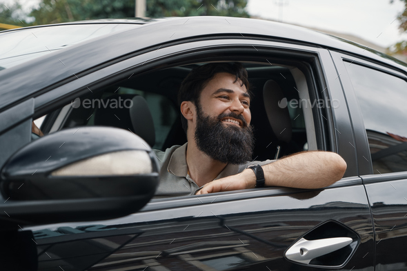 Young man smiling while driving a car - Stock Photo - Images