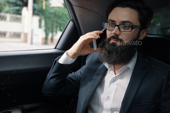 A businessman while traveling by car in the back seat using a sm - Stock Photo - Images