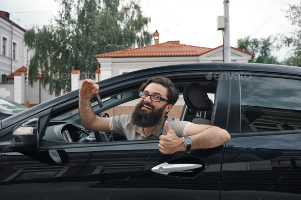 Charismatic man holding car keys showing thumbs up - Stock Photo - Images