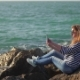 Blonde Girl with Tablet in Hands Is Sitting on a Huge Stones Shore in Sunny Summer Day - VideoHive Item for Sale