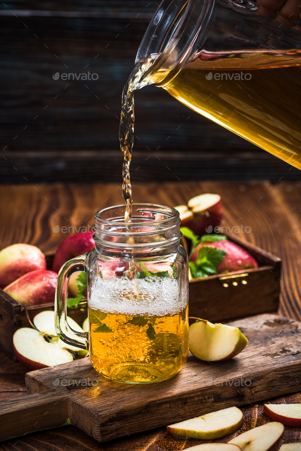 Pouring fresh and healthy apple juice into glass - Stock Photo - Images
