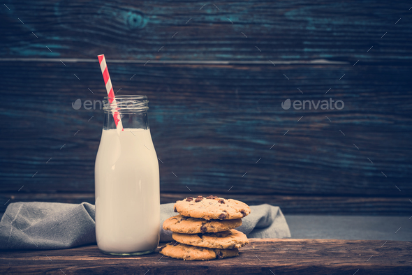 Vintage milk glass with straw and homemade cookies on wooden bac - Stock Photo - Images
