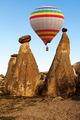 Hot air baloon flying over spectacular stone cliffs in Cappadocia - PhotoDune Item for Sale