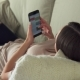 Woman Lies on Couch at Home and Using Smartphone - VideoHive Item for Sale