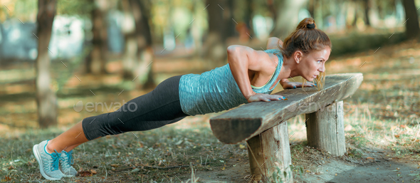 Woman doing push ups in the park, in the fall. - Stock Photo - Images