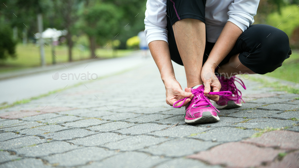 Jogger tighten her running shoe laces - Stock Photo - Images