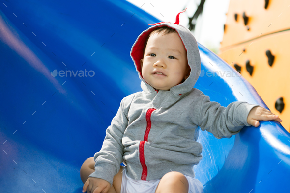 Small Asian baby boy playing slide - Stock Photo - Images