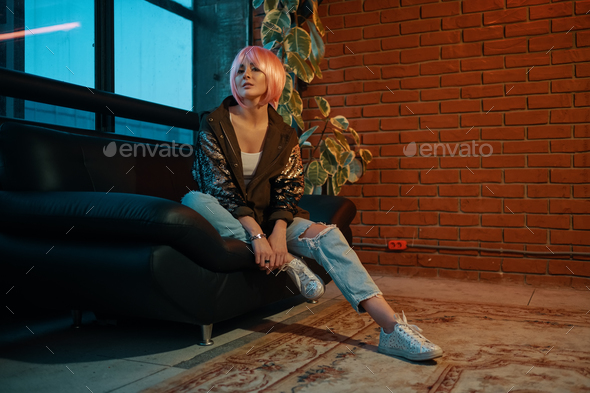 Girl with pink hair sitting relaxed on a leather sofa - Stock Photo - Images