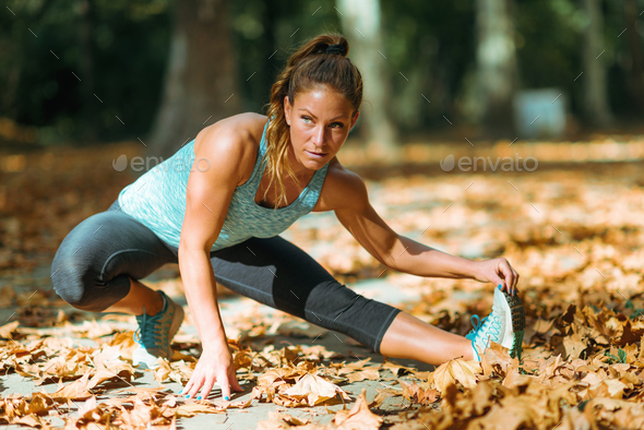 Woman stretching in the park, in the fall. - Stock Photo - Images