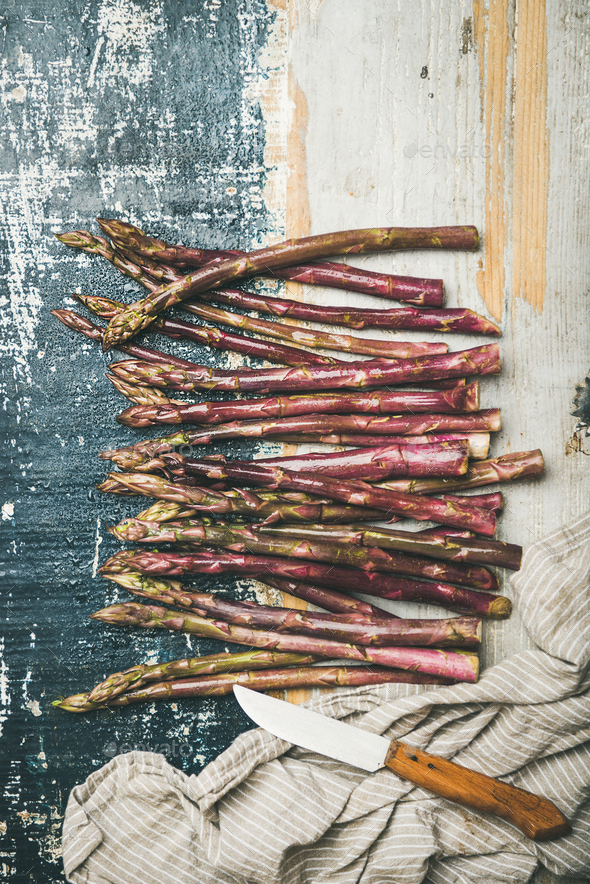 Fresh purple asparagus over rustic wooden background, vertical composition - Stock Photo - Images