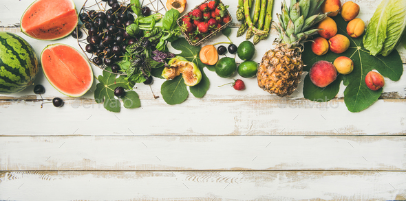 Flat-lay of seasonal fruit, vegetables and greens over wooden background - Stock Photo - Images