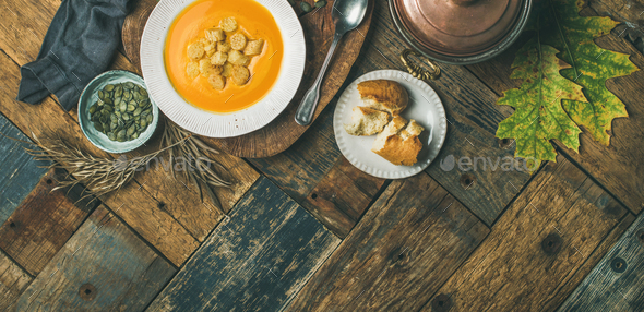 Fall pumpkin cream soup with croutons and seeds, wide composition - Stock Photo - Images