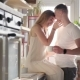 A Loving Happy Laughing Couple Is Kissing and Hugging Each Other in the Sunny Kitchen While Having a - VideoHive Item for Sale