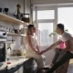 A Happy Smiling Couple Is Enjoyin the Sunny Morning in the Kitche While Sitting on the Countertops - VideoHive Item for Sale